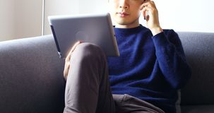 Man talking on mobile phone while using digital tablet in living room 4k. Man talking on mobile phone while using digital tablet in living room at home 4k stock video