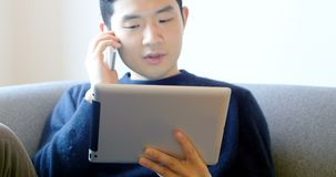Man talking on mobile phone while using digital tablet in living room 4k. Man talking on mobile phone while using digital tablet in living room at home 4k stock footage