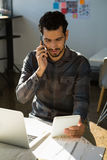 Man talking on mobile phone while using tablet at office Stock Image