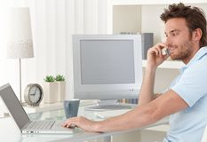 Man Talking On Phone Using Computer Royalty Free Stock Photos
