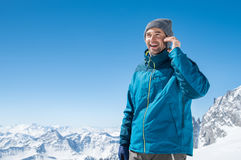 Man talking over phone in winter. Portrait of a young man talking on mobile phone on snowy mountain. Happy guy using cellphone in winter holiday with copy space stock photos