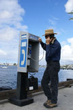 Man talking on Pay Phone. Because he has no cell phone Royalty Free Stock Image
