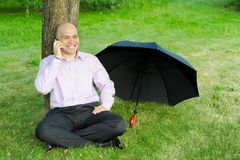Man talking on the phone. Smiling man in a green park talking on the phone Royalty Free Stock Photos