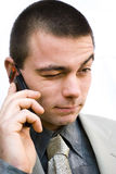 Man talking on phone. Young handsome man talking on his mobile phone making not sure face Royalty Free Stock Image