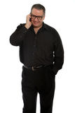 Man talking on the phone. Tall man in black talking on cellular phone Royalty Free Stock Photo