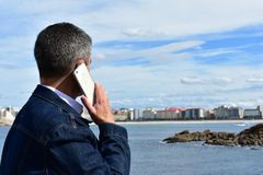 Man talking on a phone. Blue jeans clothes, white smartphone. Coastal village with beach, rocks and promenade. stock images