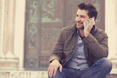 Man talking on a phone. Casual professional using smartphone smiling outside old building. Man talking on a phone. Casual professional entrepreneur using stock image