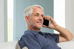 Man talking at phone. Cheerful senior man using mobile phone at home. Portrait of senior happy man talking on cellphone while sitting on sofa at home. Retired Royalty Free Stock Image