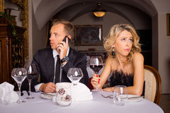 Man talking on the phone while he is on date. With woman Royalty Free Stock Photos