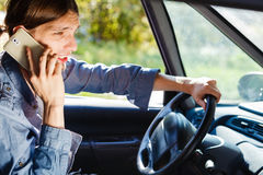 Man talking on phone while driving car. Talking while drive, danger fresh driver concept. Young man driving car using his smartphone, talking with someone Stock Photography