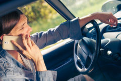 Man talking on phone while driving car. Talking while drive, danger fresh driver concept. Young man driving car using his smartphone, talking with someone royalty free stock image
