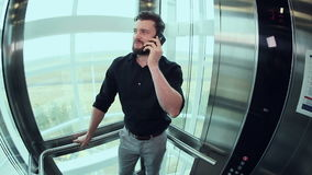 Man talking on the phone in the elevator. Young man talking on the phone in the elevator going up stock video
