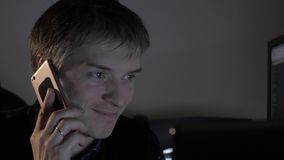 Man talking on the phone. Man in the evening at the office working on a laptop and answering phone calls stock footage