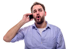 Man talking on the phone. Man with facial expression talking on cellphone against his ear Stock Photo