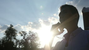 Man Talking on Phone, in front of Sun during Sunset stock video