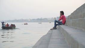 Man talking on phone at ghats of the Ganges river at sunset in Varanasi. VARANASI, INDIA - 20 FEBRUARY 2015: Man talking on phone at ghats of the Ganges river stock footage
