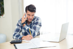 Man talking on the phone. Handsome man making notes on the bills while talking on the phone at home Royalty Free Stock Photos