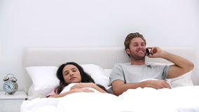 Man talking on phone while his partner is sleeping. In bed at home stock video