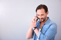 Man talking on phone and looking down Stock Images