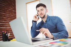 Man talking on phone in office. Confident young man talking on phone in office Stock Image