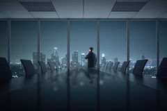 Man talking on phone in office. Young businessman talking on phone in conference room interior with table, chairs and night city view. 3D Rendering Stock Images