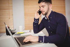 Man talking on phone at office. Young man talking on phone while working on laptop at office Stock Image
