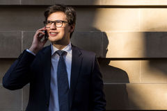 Man talking on phone outside. Handsome young businessman with glasses having mobile phone conversation outside on concrete tile background Stock Photo