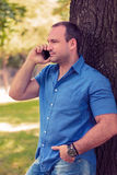 Man talking on the phone in a park. Man seriously talking on the phone in a park while holding hand in pocket Stock Photo