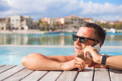 Man talking on phone while relaxing in the swimming pool Royalty Free Stock Image