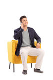 Man talking on a phone seated in a modern armchair Royalty Free Stock Photos