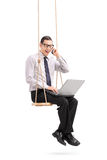 Man talking on phone seated on a swing. Vertical shot of a young man working on a laptop seated on a wooden swing and talking on his cell phone isolated on white Royalty Free Stock Photos