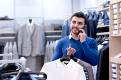 Man talking on the phone in the store. Stock Photos