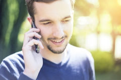 Man talking on the phone in sunny day. Man talking on the phone - against sunny day background stock photo