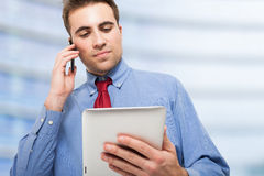 Man talking on the phone while using his tablet Royalty Free Stock Photos