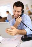 Man talking on phone and using laptop Stock Image