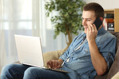 Man talking on the phone and using a laptop Stock Photos
