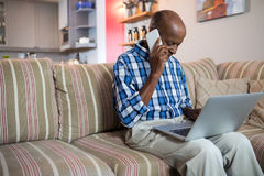 Man talking on phone while using laptop. In living room at home Stock Image