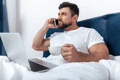 Man talking on phone, working on laptop and having morning coffee in bed Royalty Free Stock Images