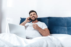 Man talking on phone, working on laptop and having morning coffee in bed Royalty Free Stock Image