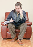 Man talking on phone and writing at home Royalty Free Stock Photography