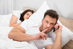 Man talking privately on cellphone. While His Wife Sleeping On Bed royalty free stock image
