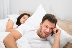 Man talking privately on cellphone. While His Wife Sleeping On Bed royalty free stock photo