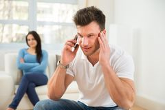Man talking privately on cellphone. Wife With Curiosity Looking At Husband Talking Privately On Cellphone Royalty Free Stock Photography