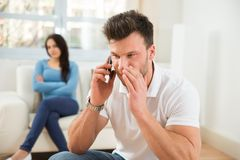 Man talking privately on cellphone. Wife With Curiosity Looking At Husband Talking Privately On Cellphone Stock Photography