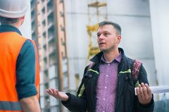 Man talking about problems at construction project to engineer. Business modern background royalty free stock images