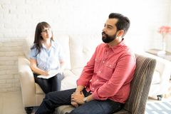 Man talking with psychiatrist during psychotherapy session. Handsome young men is sitting on chair during the psychotherapy session with female psychologist Stock Photography