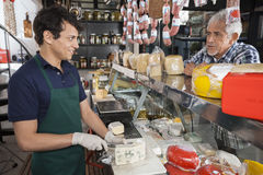 Man Talking With Salesman Slicing Cheese In Shop Royalty Free Stock Photo