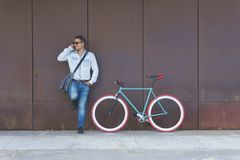 Man talking on smart phone while standing by bicycle against metallic wall at sidewalk in city royalty free stock photo