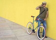 Man talking on smart phone while standing by bicycle against yellow wall at sidewalk in city stock photos