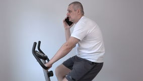 Man talking on smart phone and using exercise bike stock video footage